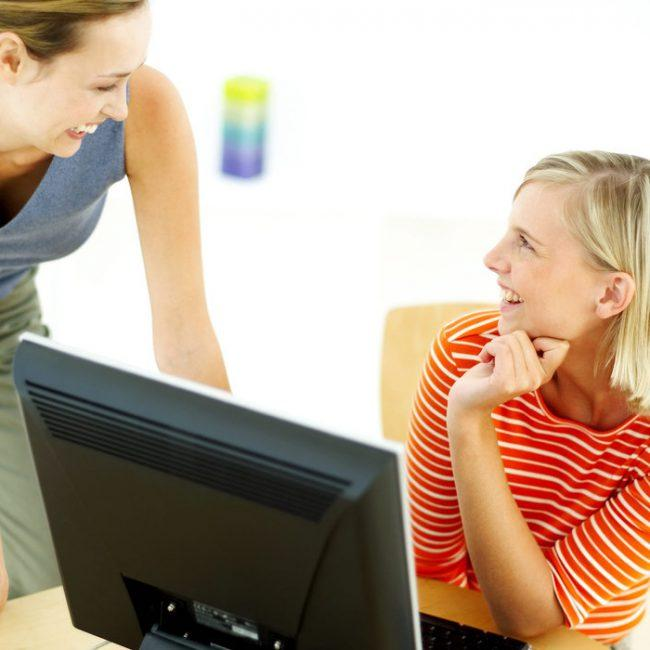Two Young Women in Front of the Computer Talking --- Image by © Royalty-Free/Corbis